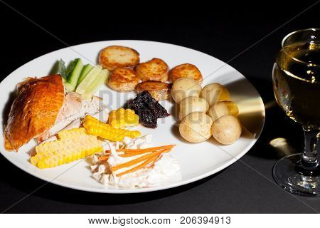 Nutritional chicken dinner meal with a glass of white wine. Low calorie healthy food on a plate. Roast chicken with sweetcorn coleslaw cranberry sauce saute and boiled potatoes and cucumber.