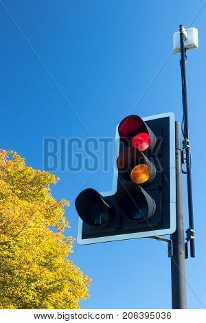 British road traffic light with signal on red and amber. Lights with traffic sensor against blue sky with copy space.