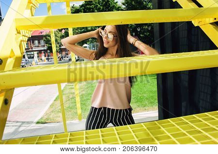 A Beautiful Girl With Sunglasses In A Beige T-shirt And Black Breeches In A White Stripe. Against Th