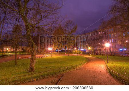 Dusk autumn view of park and footpath Yusupov Garden and illuminated Sadovaya Street Saint Petersburg Russia