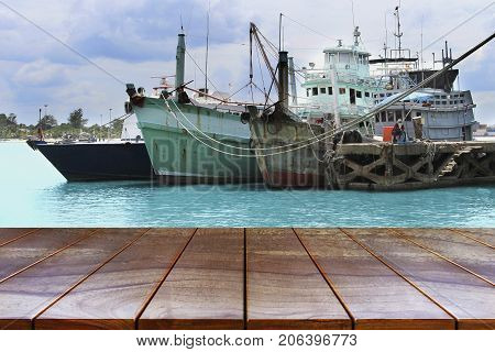 Empty wooden table space platform and Boats on the sea and sky background for product display montage Wood table for product placement.