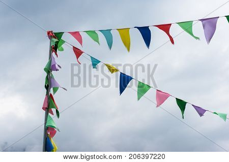 Colorful string pennant flags or string flags prayer banner against clouds on the background
