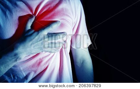 man guy in a white t shirt on a black background in a blue color hold hands on his heart heart atack severe heartache chest myocardial infarction