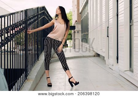 Beautiful young woman standing at the entrance to the underground garage. The model wears stylish clothes a beige jersey and black breeches in a white stripe. The girl is looking up the hair is developing in the wind. Women's fashion. Urban way of life.
