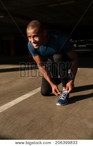 Portrait of a smiling happy afro american sportsman tying his shoelaces while sitting and looking away indoors