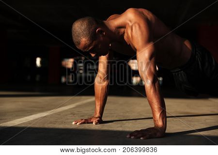 Close up portrait of a half naked muscular fitness man doing plank exercises indoors