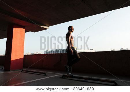 Full length portrait of a half naked young afro american sportsman walking indoors