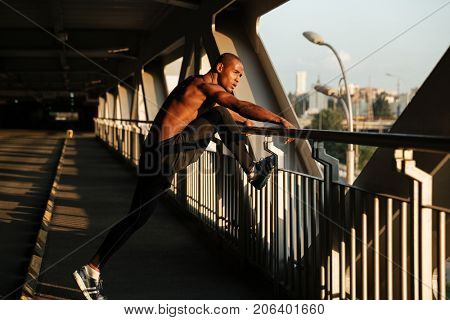Full length portrait of a young motivated half naked african sportsman doing stretching exercises while leaning on a handrail indoors