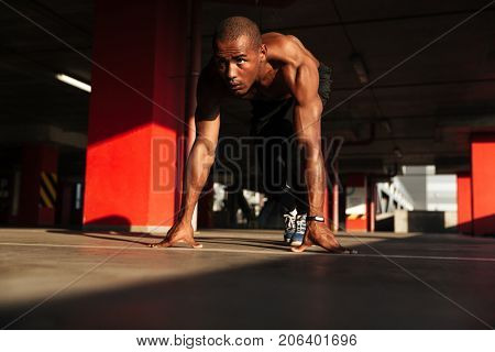 Portrait of a concentrated young half naked african sportsman getting ready to run indoors