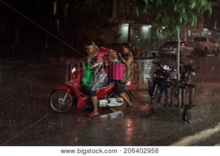 BANGKOK THAILAND - AUGUST 08: An unidentified motorcycle taxi assists his unidentified passenger in carrying a pink plastic bucket as he tries to ride in heavy rain on August 08 2017 in Bangkok.