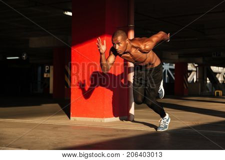Full length portrait of a young muscular half naked african sportsman starting to run indoors