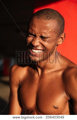 Close up portrait of a smiling happy half naked african sportsman laughing while standing indoors
