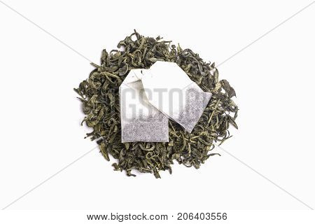 Green tea leaves and sachets of black tea isolated on white background
