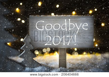 Sign With English Text Goodbye 2017. White Christmas Tree With Snow And Magic Glowing Lights In Backround And Snowflakes. Card For Seasons Greetings.