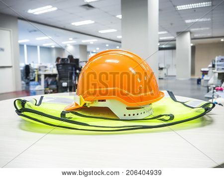 The orange safety helmet on wood table in officeconcept security and protection