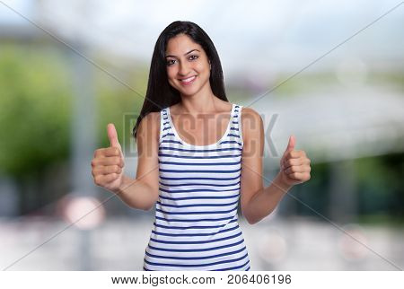 Laughing turkish woman in a summer shirt showing both thumbs up