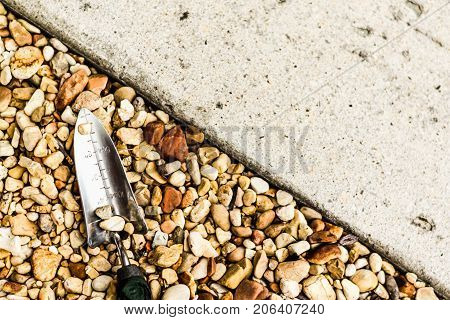 Gardening Trowel in Pebbles along a Driveway