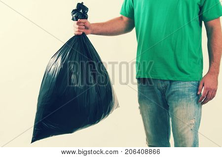 a man holding a trash bag with garbage.