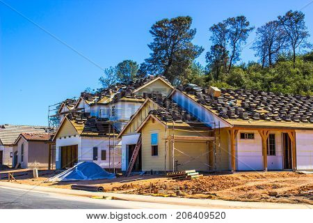 New Homes Under Construction With Materials On Roof