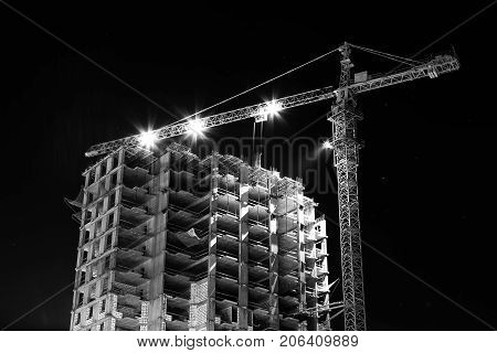 Construction building site with tower cranes building under construction lighted with projectors at night from low angle