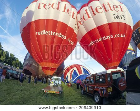 Bristol, Somerset, UK: August 13, 2016: Inflating the balloons for a mass ascent at the Bristol International Balloon Fiesta. Two of the balloons are advertising Red Letter Days.