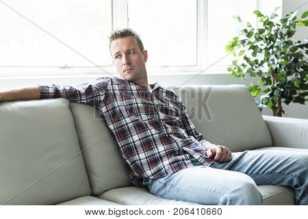 A Depressed man thinking on the sofa alone at home