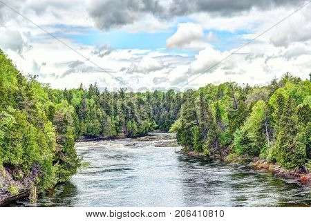Montmorency River In Boischatel Town, City Of Quebec Landscape During Cloudy, Overcast Day With Pine