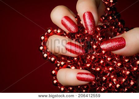 Female hand with glittered dark red nails is holding red pearls on dark red background manicure concept.