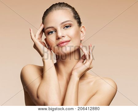 Smiling attractive woman touching her clean skin face. Photo of young woman of european appearance on beige background. Youth and skin care concept