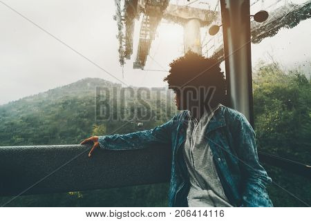 Silhouette of young curly black girl in jeans jacket sitting inside of cabin of mountain lift smiling and looking aside on beautiful rainy hills of Rosa Khutor resort Sochi Russia