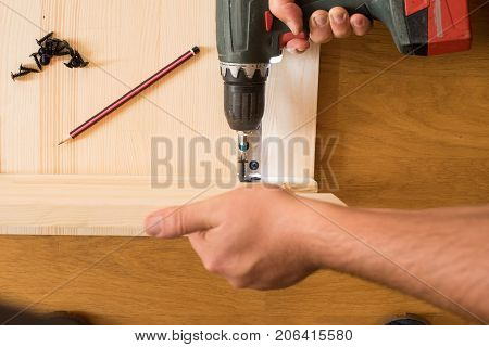 Cordless screwdriver holding by hand. Construction worker holding the hand drill. Screwdriver in the hand of the master. Carpenter working with an electric screwdriver  using a cordless screwdrive