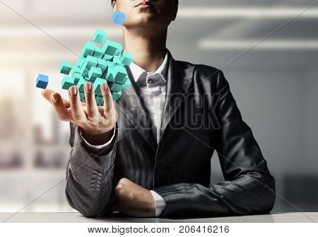 Cropped image of business woman in suit presenting multiple cubes in hand as symbol of innovations. Office view on background. 3D rendering.