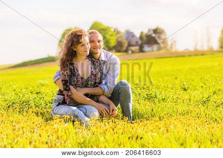 Young happy smiling couple sitting in yellow dandelion flower farm field during sunset by countryside rural house in Ile D'Orleans Quebec Canada