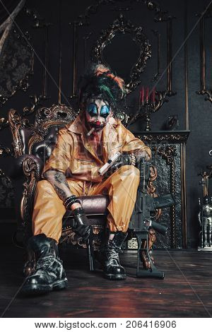 Evil clown man stained in blood is sitting with guns in a room with vintage interior. Halloween. Horror, thriller film.