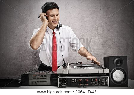 Formally dressed man playing music on a turntable against a rusty gray wall
