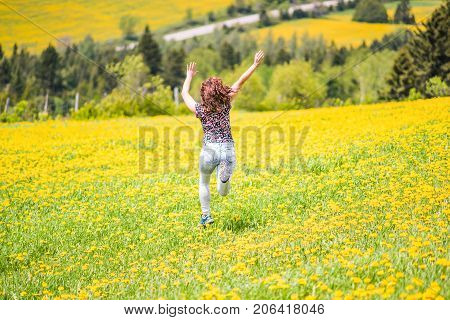 Back Of Young Woman Running, Jumping In Air And Smiling On Countryside Yellow Dandelion Flower Field