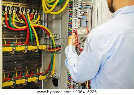 Engineer with multimeter in high voltage panel.