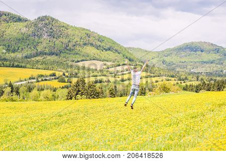 Young Man, Male Running, Jumping, Hanging In Air, Mid-air And Smiling On Countryside Yellow Dandelio