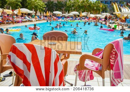 Alanya Turkey - August 14 2017: Tourists are bathing in swimming pool of resort hotel. table near pool with slides. Happy summer vacation. Swimming pool with water park.