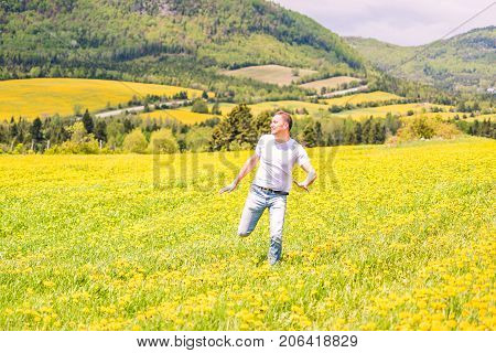 Young Man Running, Jumping In Air And Smiling On Countryside Yellow Dandelion Flower Fields In Summe