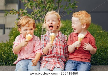 Group portrait of three white Caucasian cute adorable funny children toddlers sitting together sharing ice-cream food. Love friendship fun concept. Best friends forever.