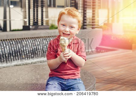 Portrait of cute white Caucasian redhead blond preschool boy with blue eyes in red t-shirt eating licking ice cream in waffle cone. Copyspace for text. Light sun leak beam on a side.