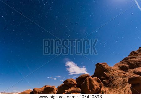 Night Sky With Full Moon Rising, Or Moonrise, In Goblin Valley State Park In Utah Showing Clouds, St
