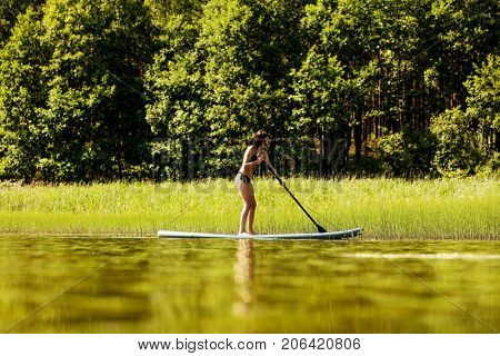 Young attractive woman on stand up paddle board