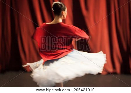 ballet, mystic, rehearsal concept. tender and phantom figure of ballerina, photographed out of focus, spinning around herself and her bright red shirt blending in with the curtains of theater