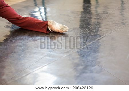dancing, pation, strength concept. close up of muscular leg of man who dancing in the class for rehearsal wearing in burgundy-red sweatpants and light-pink satin pointe shoes