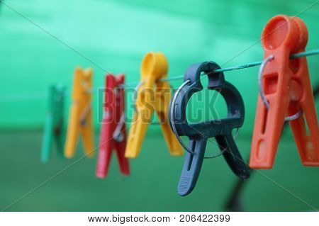 Different shaped colorful clothespins hanging on the clothesline.