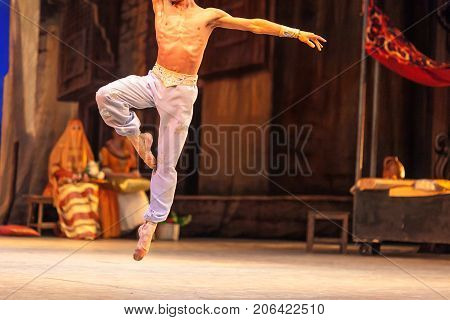entertainment, ballet, culture concept. strong body with a six pack of abs of ballet dancer, who dressed in silky pants only, tensing up when he leaping high