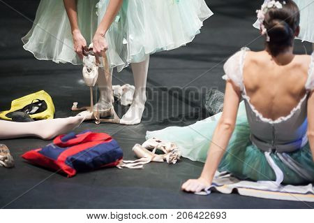 preparation, backstage, passion concept. on the stage of the theater female ballet dancers preparing to final rehearsal, wearing pointe shoes, putting ribbons and warming up