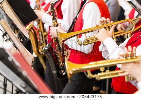 musical instrument, brass band and orchestra concept - closeup ensemble of musicians playing on trumpets and saxophones in red concert costumes, male hands with shiny equipment, selective focus